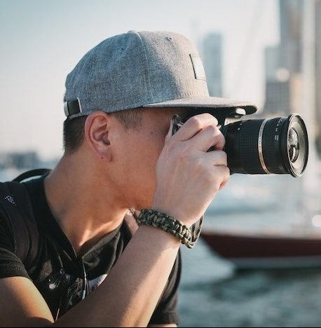 young man taking pictures of city