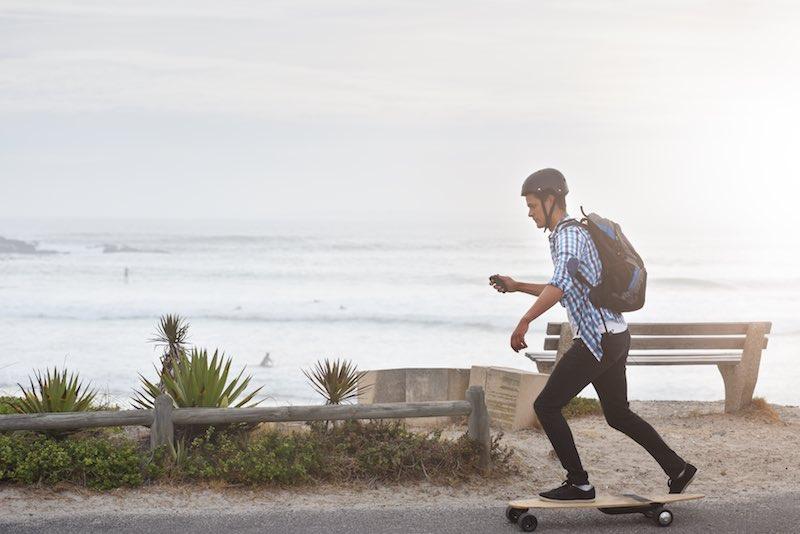 Young man riding electric skateboard on a beach sidewalk