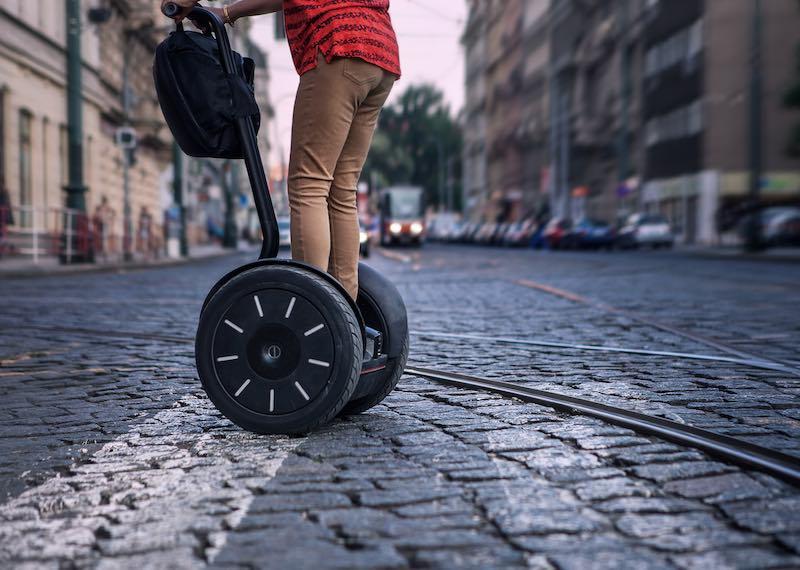Electric Tranportation. Person riding on a Segway E+ on a paved city street