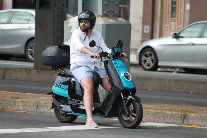 Bearded man on a blue electric moped scooter wearing helmet
