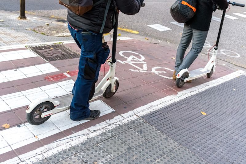 Two men riding white electric scooters on a city bicycle track