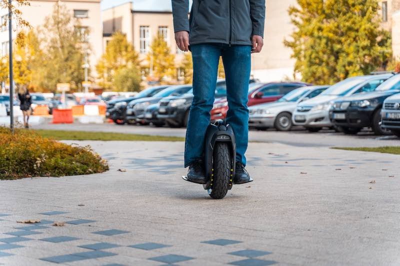 Man riding an electric unicycle on the sidewalk
