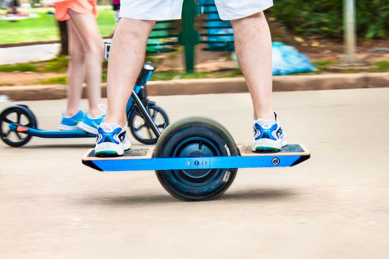 Man riding onewheel on a park pathway. Electric transportation