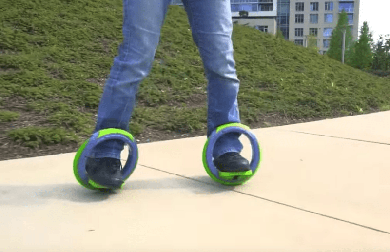 person riding a set of electric orbit wheels on a sidewalk in the park