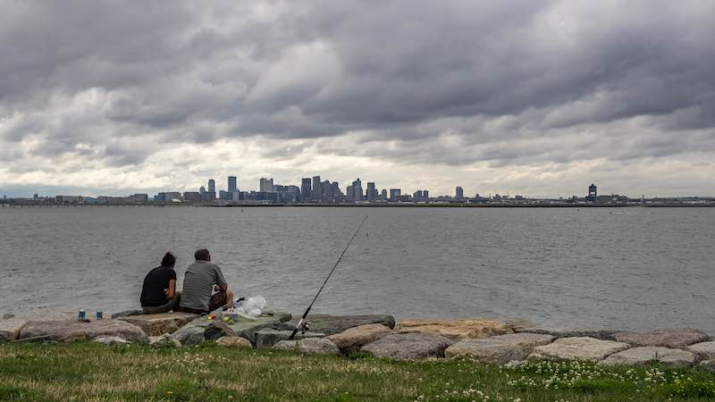 Two fishermen fishing in Boston, near downtown