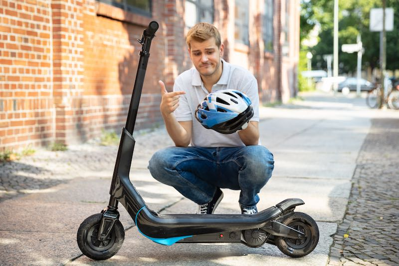 young man holding a helmet while standing by an electric scooter