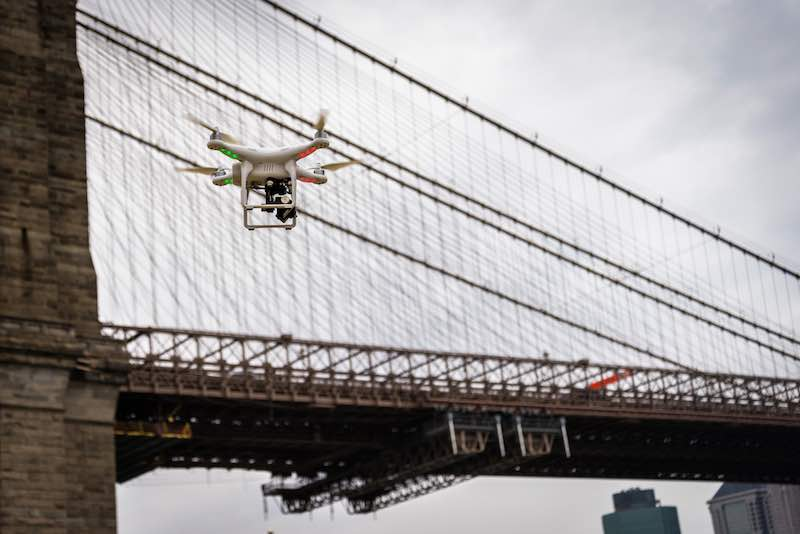 White Drone Flying In New York City by the Brooklyn Bridge