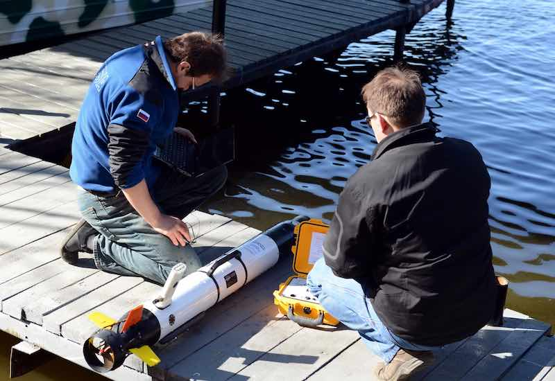 Two Men Preparing to launch an underwater drone