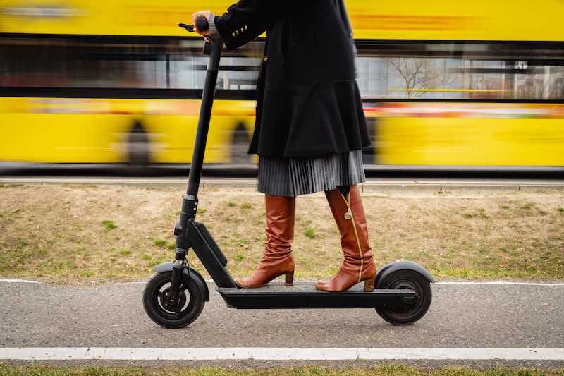 Lady wearing boots on electric scooter passing by a yellow train