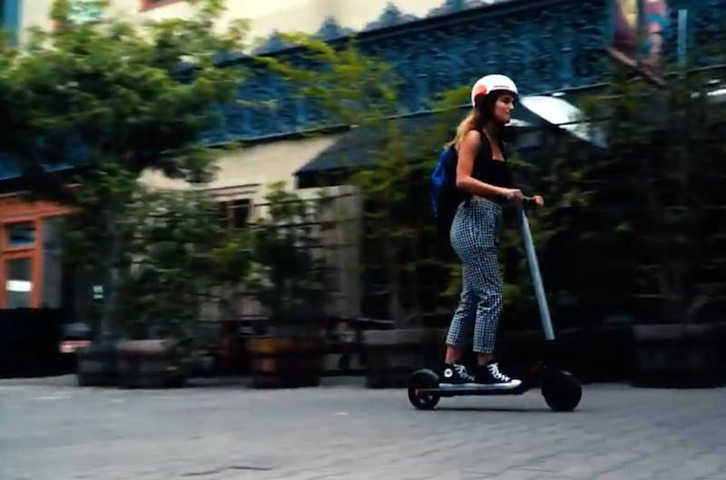 Young lady riding the Segway Ninebot Electric scooter and wearing Ninebot Helmet