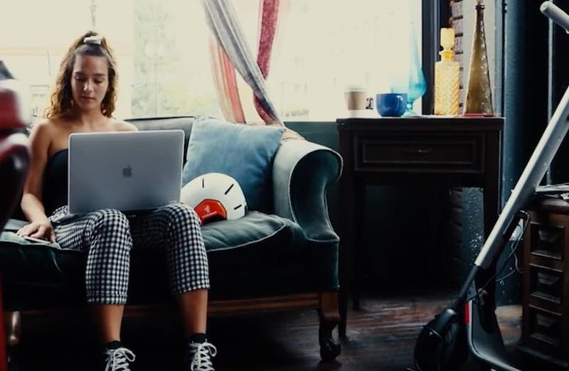 Young lady typing on laptop computer on a couch by the Segway Ninebot Helmet