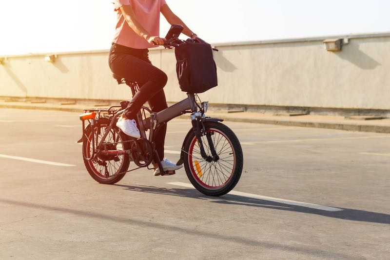Young lady wearing a pink t-shirt riding an electric folding bicycle